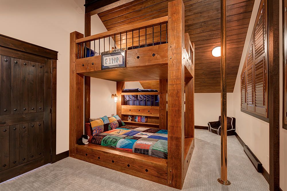 Custom bunk beds with rough cut timbers and fireman's pole.